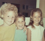 Me, my brother, and my sister. Small-kid time. Summer suntans, my favorite dress with the bell sleeves. Circa '66. Yes, I have had this hair my entire life.