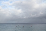 Old Dudes on their SUPs in Waimea Bay on an overcast morning.