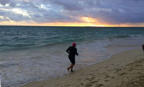 Running to swim lap two as the sun rises in the east. Mahalo for the photo by Kim Burnett.